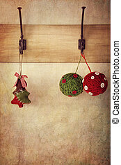 Holiday ornaments hanging on antique wall hooks