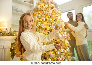 Holiday. Pretty fair-haired girl decorating new year tree with her parents
