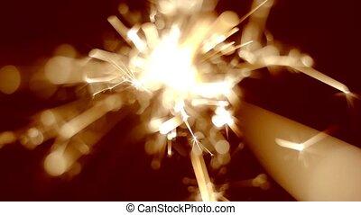 Holiday sparkler burning in macro shot toned in vintage gold...