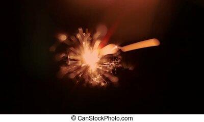 Holiday sparkler on dark of amber color