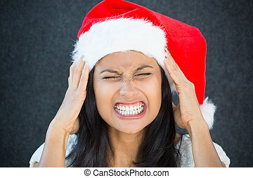 Closeup portrait, young beautiful worried stressed wife, mother, woman in santa claus hat with hands on temples about to break down, isolated gray black background. Last minute christmas shopping