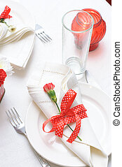 Holiday tableware in red and white colors with ribbons and flowers
