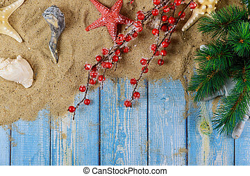 Holiday vacation with starfishand sea shells on a branch of christmas tree with blue wooden background
