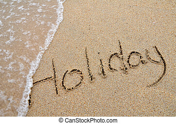 Holiday word written on sandy beach