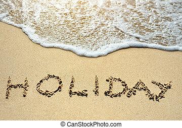 holiday written on the sand beach near sea