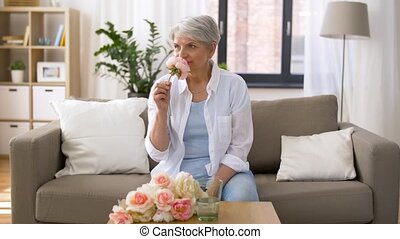 happy senior woman putting flowers to vase at home -...