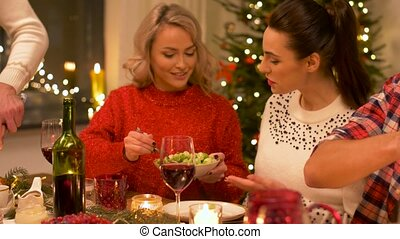 happy friends having christmas dinner at home