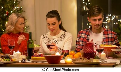 happy friends having christmas dinner at home - holidays and...