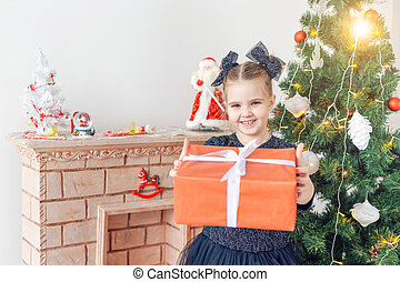 Holidays and childhood concept - Portrait of little happy cute child girl with Christmas present