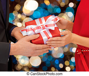 close up of couple hands holding gift box