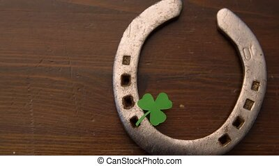 horseshoe with shamrock on wooden background - holidays and...