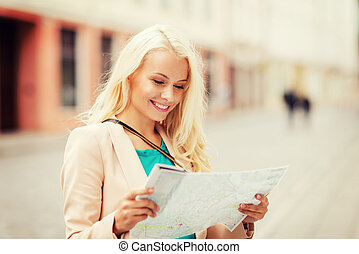 girl looking into tourist map in the city