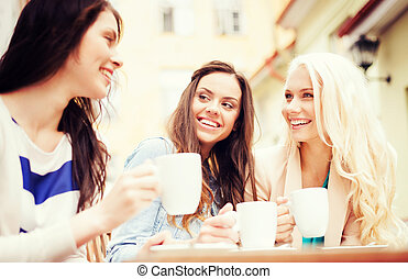 beautiful girls drinking coffee in cafe - holidays and...