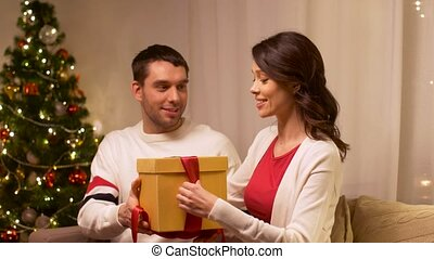 happy couple with christmas gift at home - holidays,...