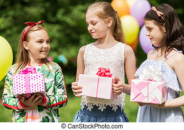 girls with gifts on birthday party at summer