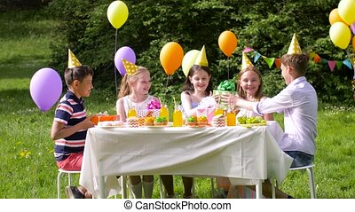 happy kids with gifts on birthday party at summer -...