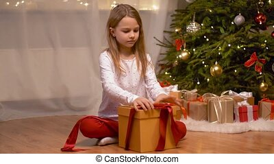 happy girl opening christmas gift at home - holidays,...