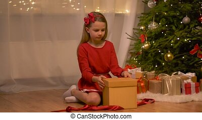 happy girl opening christmas gift at home