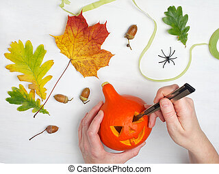 holidays, halloween, decoration and people concept - close up of woman hands with pumpkin on white wooden background