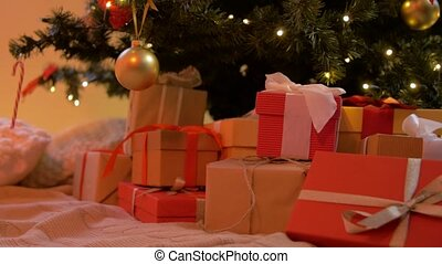 gift boxes under decorated christmas tree at home - holidays...