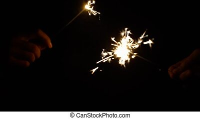 hands playing with burning sparklers in darkness - holidays,...