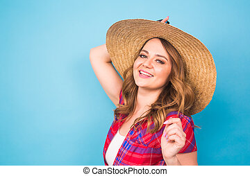 Holidays, summer, fashion and people concept - Girl in fashionable clothes straw hat. Portrait of charming woman on blue background with empty copy space