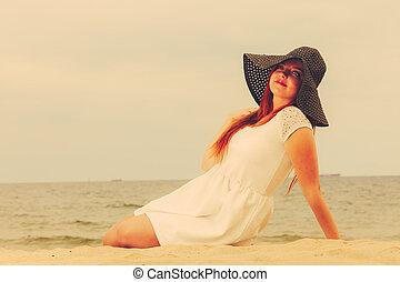 happy girl in black hat on beach.