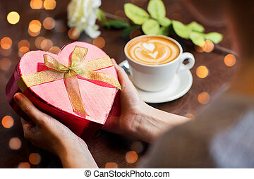 close up of hands holding heart shaped gift box