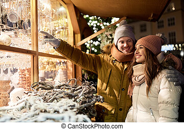 happy couple at christmas market shop window - holidays, ...