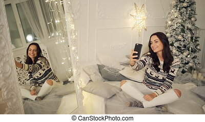 holidays, winter and people concept - happy young woman taking selfie over christmas tree at home