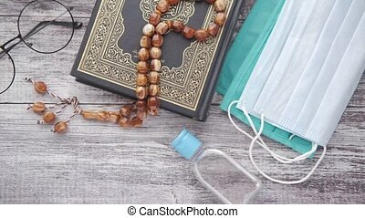 holly book of quran, prayer rosary , hand sanitizer and mask on floor ,