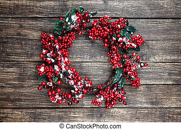 Holly christmas wreath on wooden table.