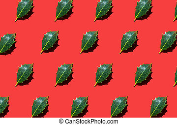 Holly leaves lying diagonally on red background.