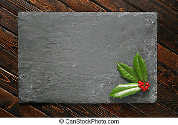 Holly with berries on dark stone background