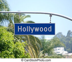 Hollywood Blvd sign with palm tree backdrop.