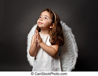 Little white angel child with hands together in devotional prayer and looking heavenward with hope and faith.