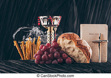holy bible and christian cross with candles and chalice on dark striped table for Holy Communion