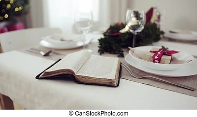Holy bible book on a table set for a dinner at home at...