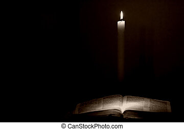 A single candle lights a Holy Bible in a dark room (vintage tone).