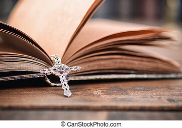 Holy Bible, Christian cross necklace on a wooden background.