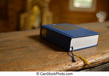 Holy Bible lying on a bench in church