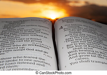 Holy Bible opened at sunset, highlighted in Malachi chapter 4 verse 2. Background with sun rays and clouds