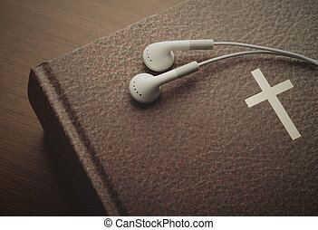 Holy Bible with a resting pair of earbuds over it. The word...