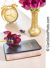 Holy Bible with flowers on wooden table