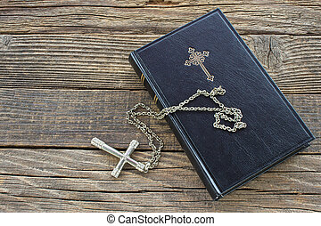 Holy bible with silver cross on wooden background