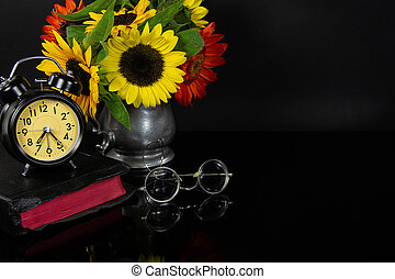 Holy Bible with sunflowers and clock