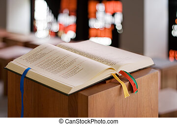 Open bible on a wooden console in small modern chapel.
