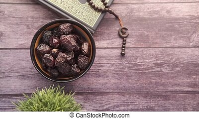 Holy book Quran, rosary and date fruit on table with copy space ,
