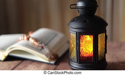 Holy book Quran, rosary and leathern lamp on table, .