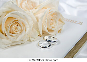 White roses and silver rings on Bible.
